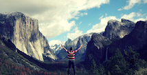 Man looking over mountain range with arms wide open