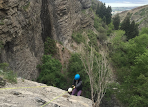Person climbing over cliffside
