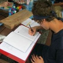 Teen writing in notebook at desk