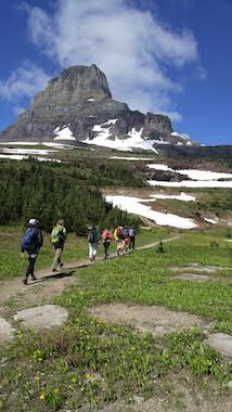 Groups of people hiking across mountain side