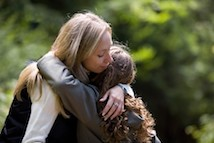 Woman and student hugging