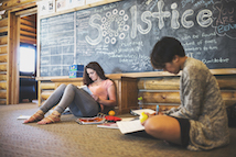 Two students sitting on the floor studying