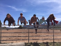 Group of teens jumping over fence