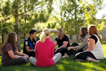 Group of teens sitting in a circle on the grass