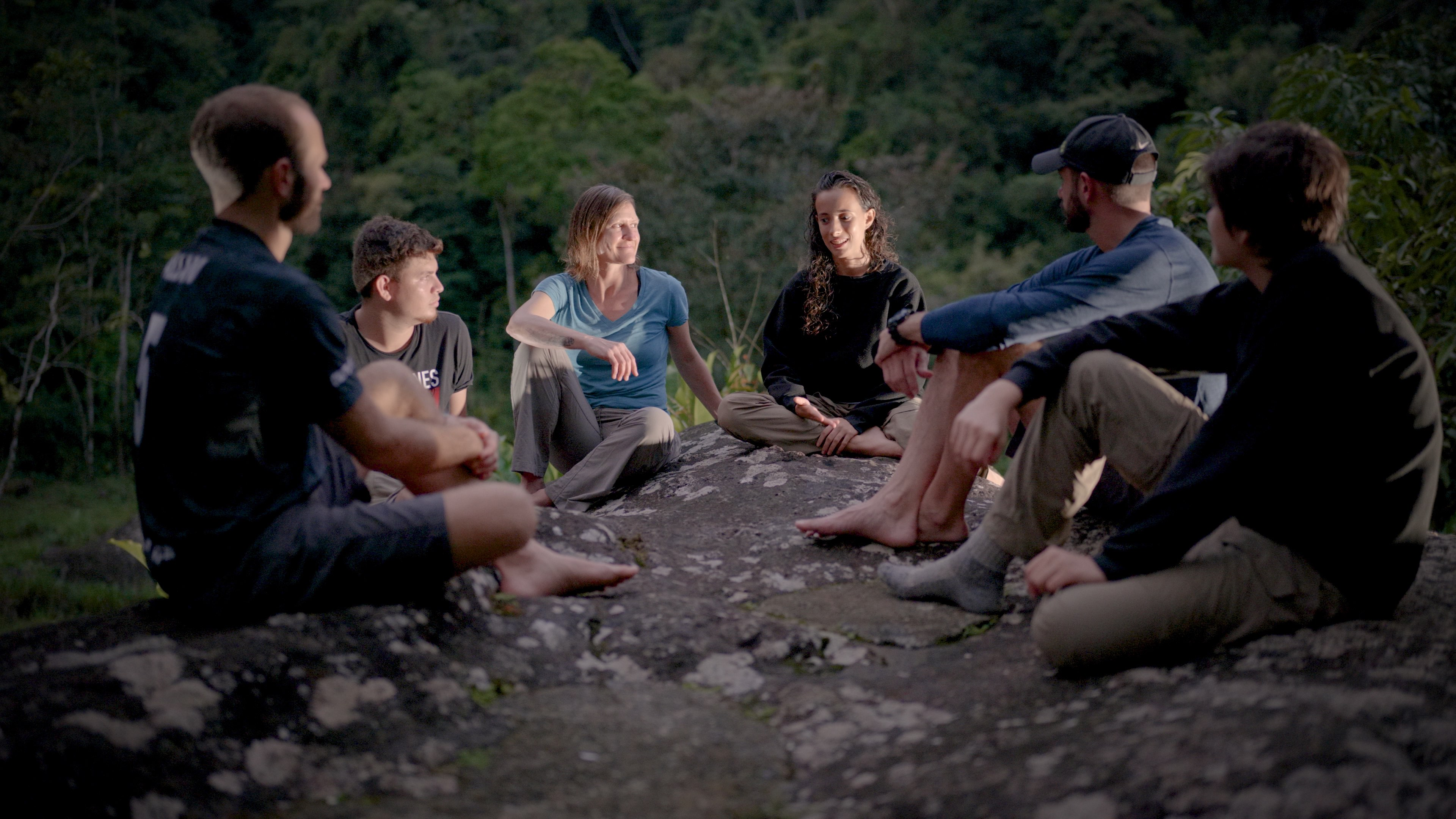 Group of teens in therapy sitting around a camp fire