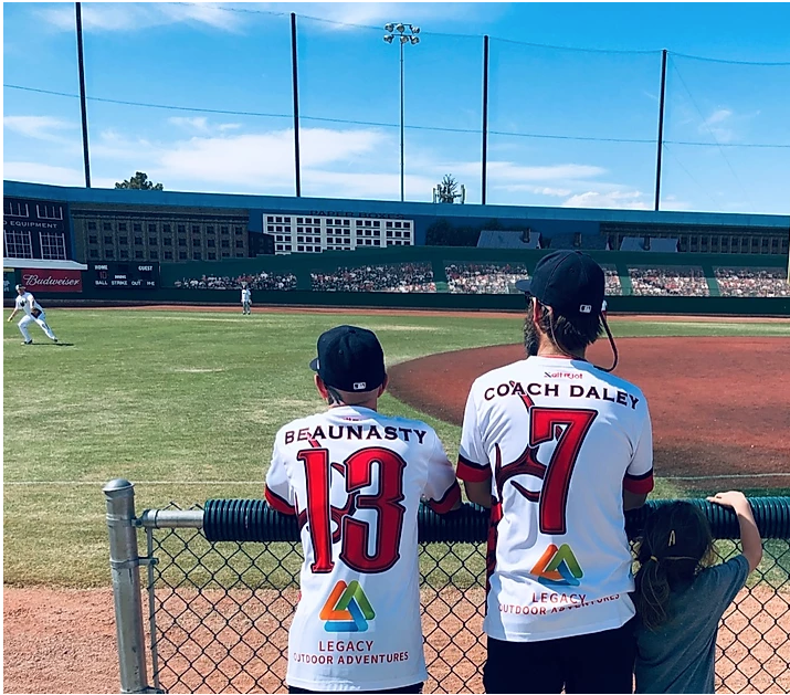 Two softball players watching a game in progress
