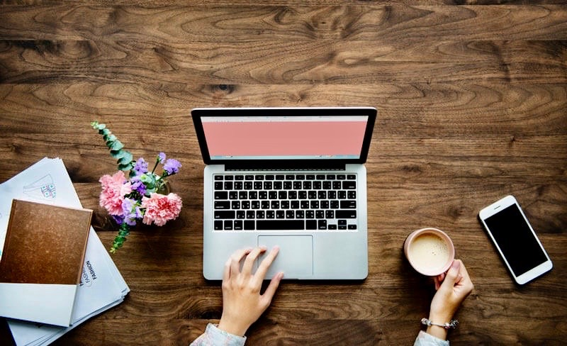 Woman working at her laptop with morning coffee