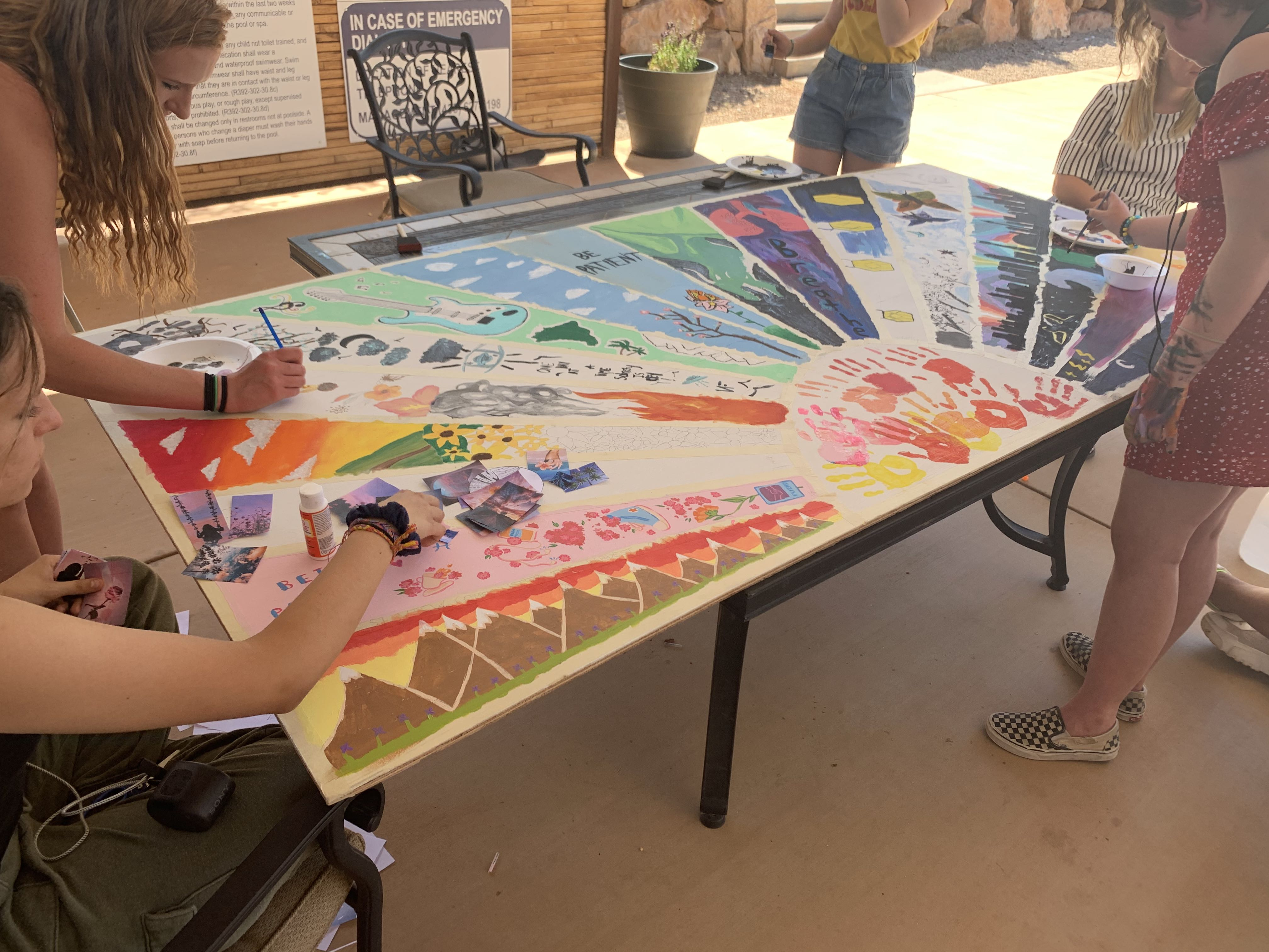 Teens contributing to a poster commemorating 20 years