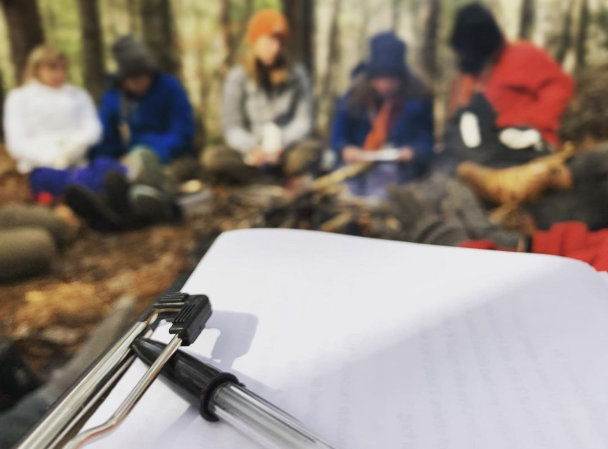 Picture of students sitting in the wilderness with a clipboard for schoolwork.