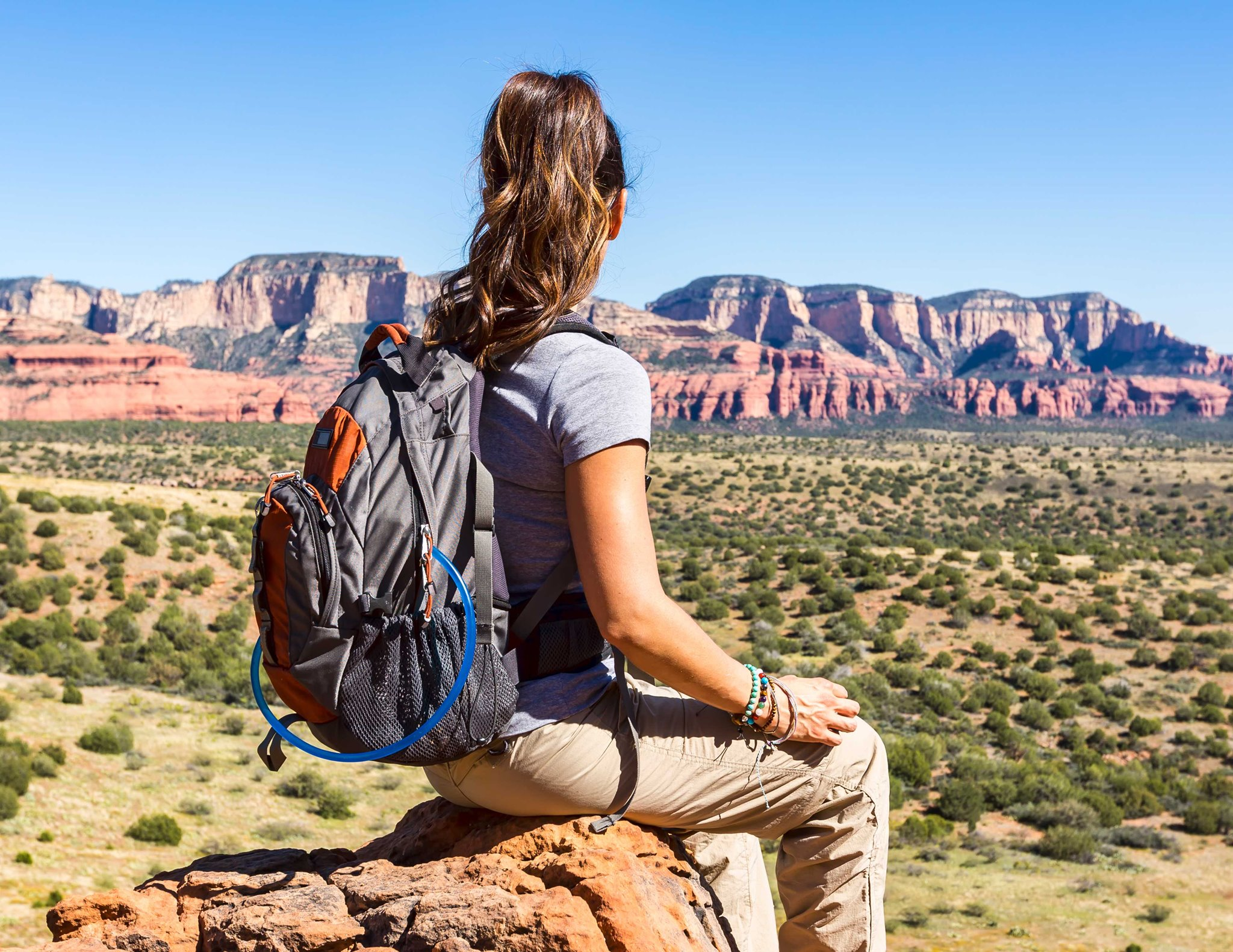 Photo of a young woman from the back with a backpack on looking out at Utah mountains.
