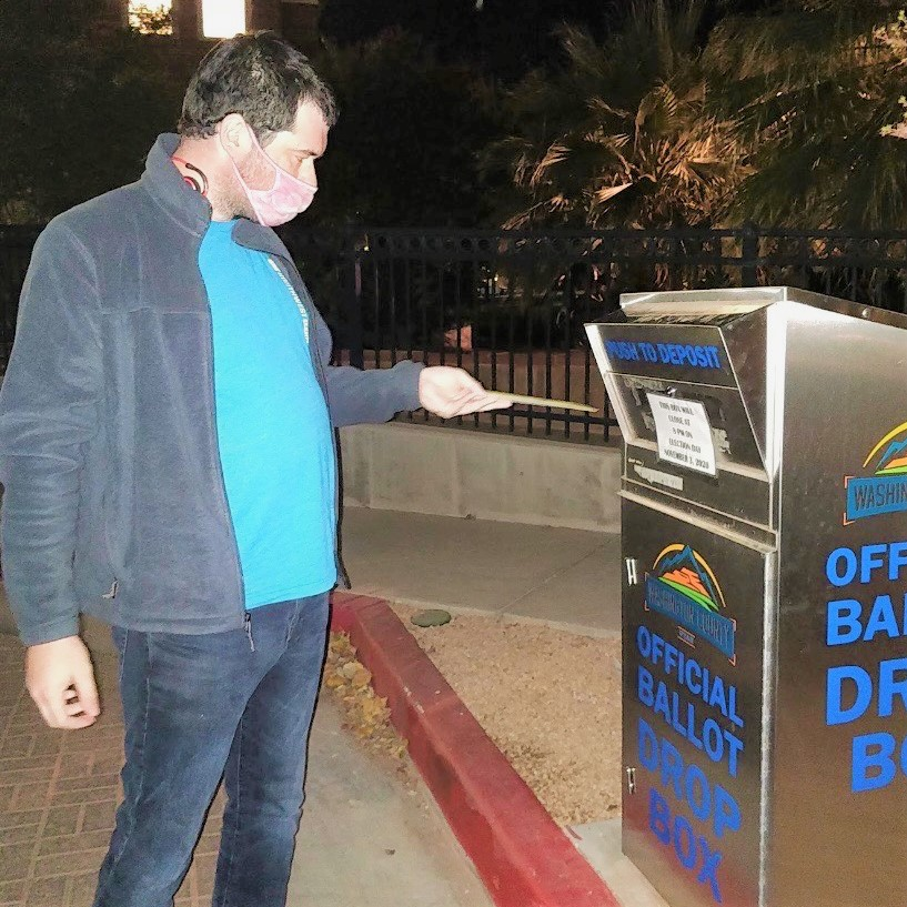 photo of a young adult with a mask on dropping a ballot into an official ballot dropbox.